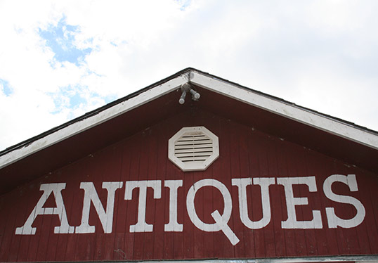 Red Barn with white lettering saying Antiques