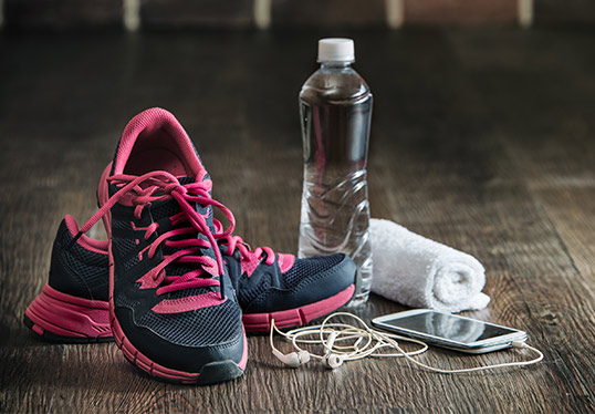 running shoes, bottle of water, and device with headphones