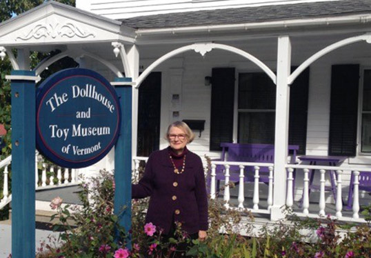 dollhouse museum owner posing in front of sign