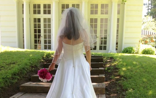 Back of a bride in her gown with veil and flowers at vermont destination wedding location Four Chiimneys Inn