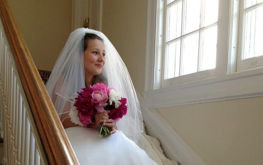 Happy bride on the stairs at Four Chimney's Inn