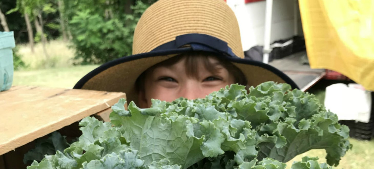 young boy in hat peaking behind kale leaves at bennington farmers' market