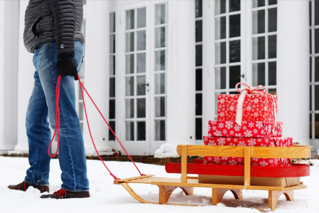 man-pulling-sled-with-stack-of-gifts