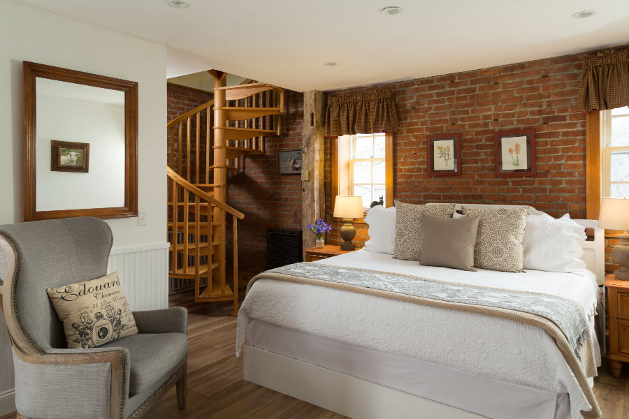 Four Chimney's Room with brick wall and spiral staircase