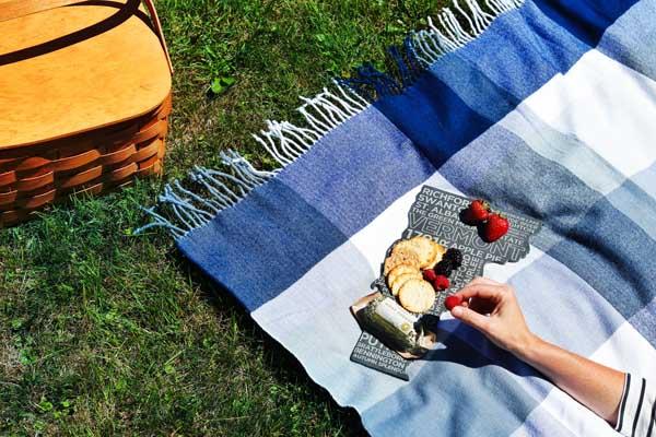 picnic scene vermont cheese board woman grabbing berry