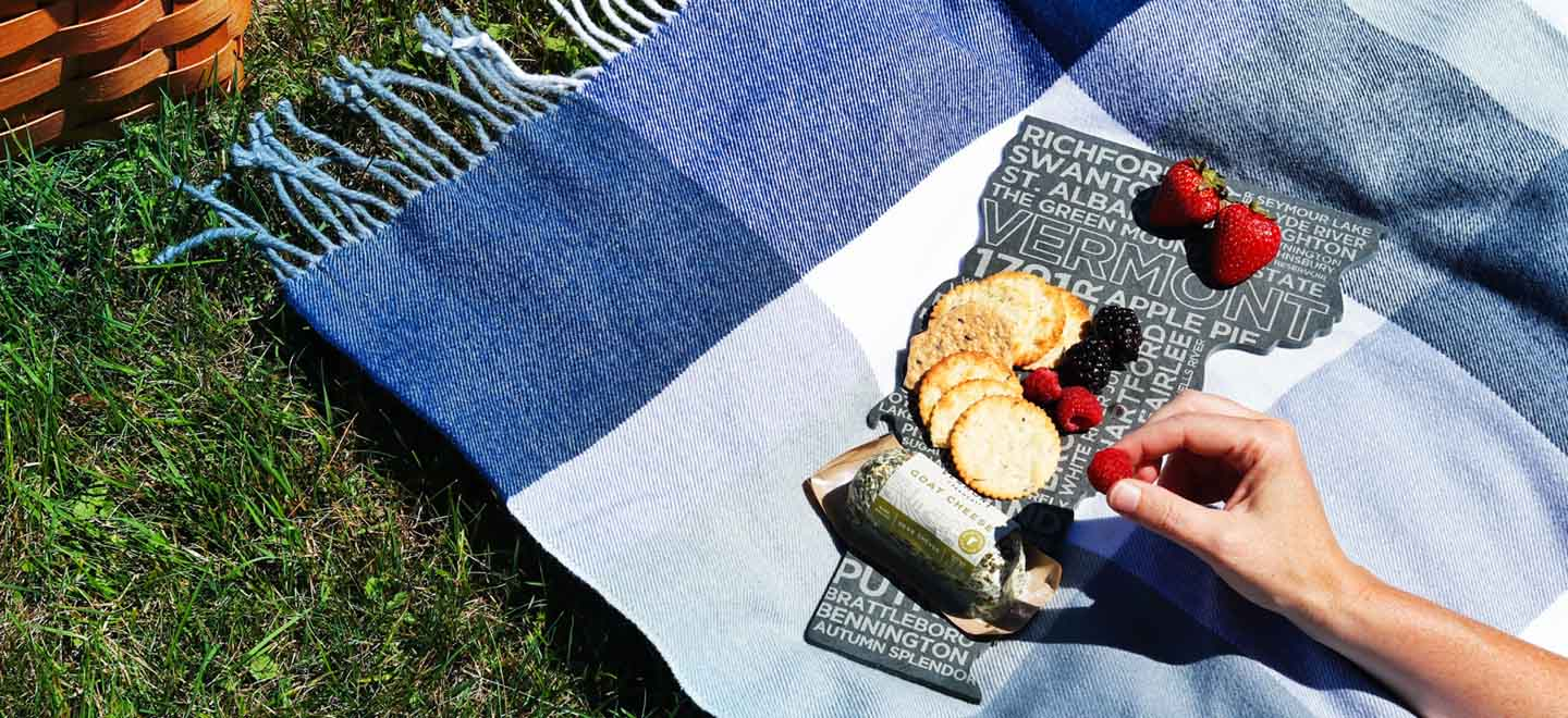 picnic scene woman picking up berry from cheese plate