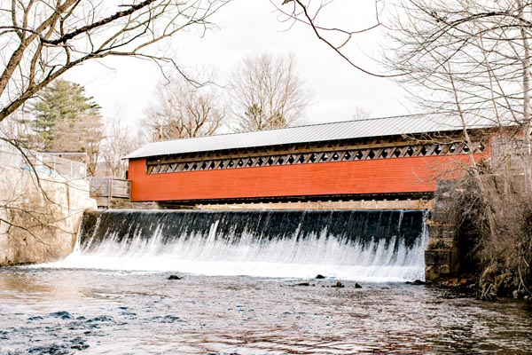 Vermont covered bridge in snow waterfall